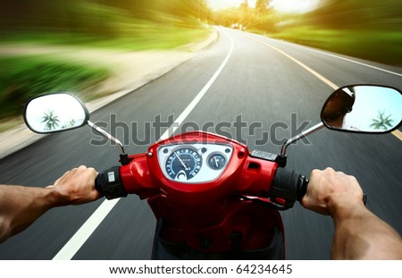 Driving a motorbike on an asphalt road - stock photo