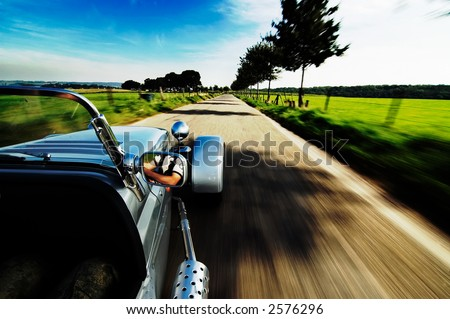 Driving a sports-car on a road - stock photo