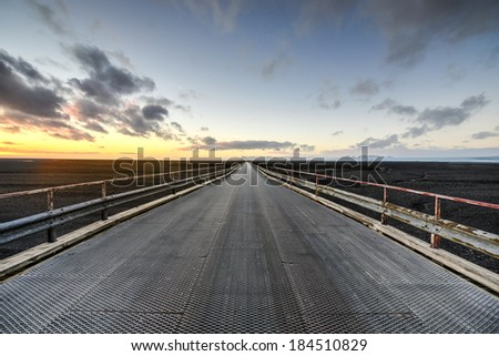 Driving across a volcanic landscape on Highway 1, the ring-road in Iceland at sunset. - stock photo