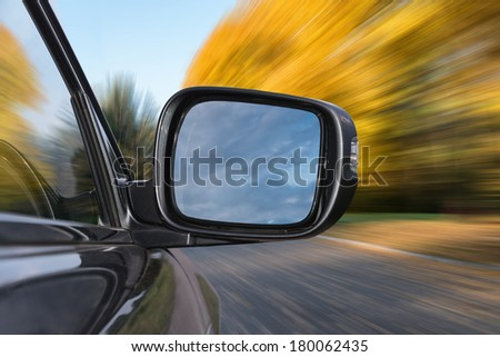 Driving along a country road at sunny fall day - stock photo