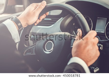 Driving concept. Close-up of man in formalwear driving car