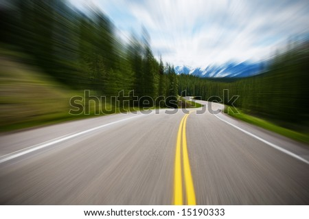 driving fast in a car on a road - stock photo