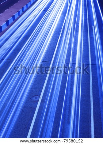 Driving fast lights trails from cars, blue toned - stock photo