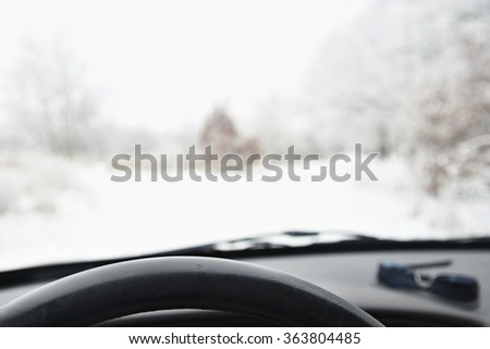 Driving from the driver's perspective in bad weather in the snow. Winter automobile background. - stock photo