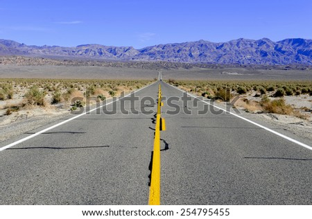 Driving in barren desert landscape through Death Valley, California