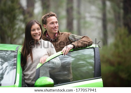 Driving in car - driver couple resting looking in forest taking break in green rental cars during during road trip travel vacation holiday in beautiful landscape nature. Asian woman, Caucasian man.