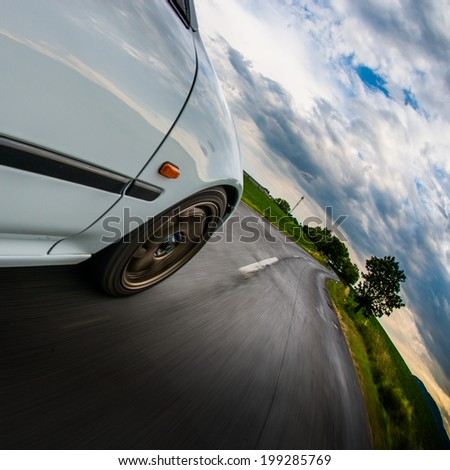 Driving in the curve - Front side view of white car driving fast. - stock photo