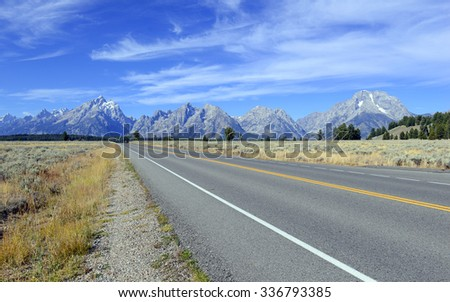 Driving in the Teton Range and Rocky Mountains in the American West, USA - stock photo