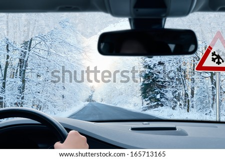 driving in winter - country road in winter - risk of snow and ice - stock photo