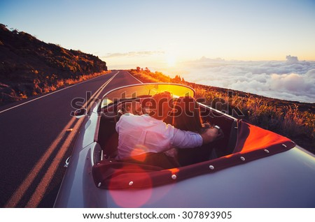 Driving into the Sunset. Romantic Young Couple Enjoying Sunset Drive in Classic Vintage Sports Car - stock photo