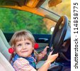 Driving little girl. Beautiful child in a car - stock photo