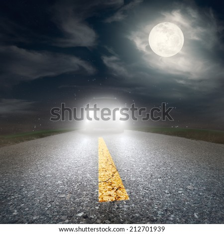Driving on an asphalt road towards the headlights of car at night  - stock photo