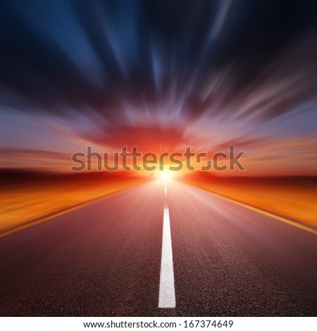 Driving on an blurred empty asphalt road at sunset - stock photo
