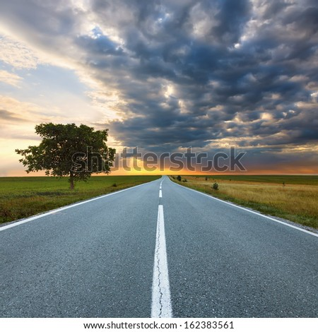 Driving on an empty asphalt road at dawn - stock photo