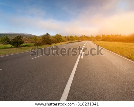 Driving on an empty asphalt road through idyllic countryside scenery. - stock photo