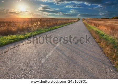 Driving on an empty asphalt road through the agricultural area at sunset. - stock photo