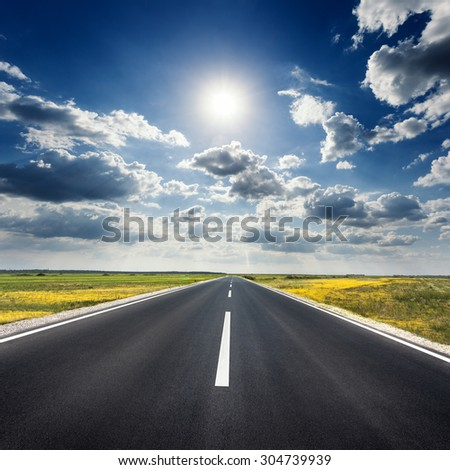 Driving on an empty asphalt road through the agricultural fields at idyllic sunny day towards the sun.