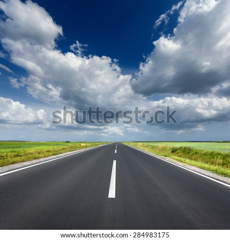 Driving on an empty asphalt road through the agricultural fields at sunny day.