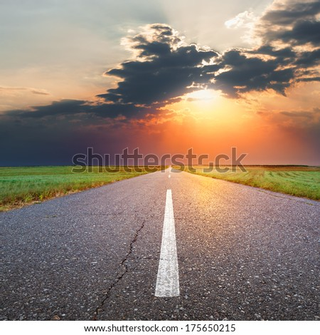 Driving on an empty asphalt road through the agricultural fields at sunset