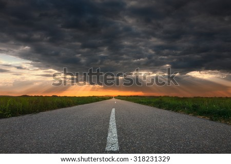 Driving on an empty asphalt road through the countryside fields towards the setting sun and sunbeams.