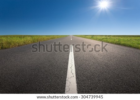 Driving on an empty asphalt road through the cultivated fields at idyllic sunny day.