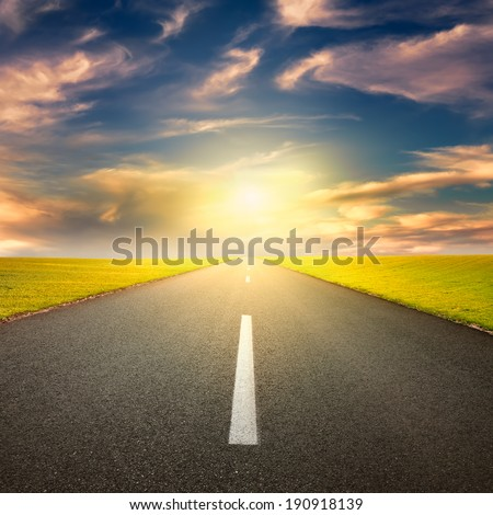 Driving on an empty asphalt road through the idyllic rural landscapes at sunset