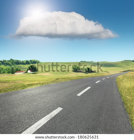 Driving on an empty asphalt road through the idyllic rural scenery - stock photo