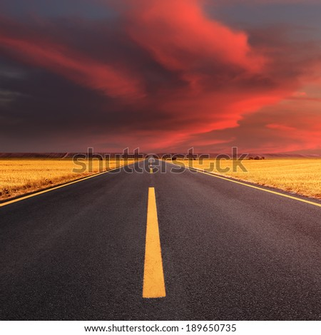 Driving on an empty asphalt road through the wheat fields at sunset