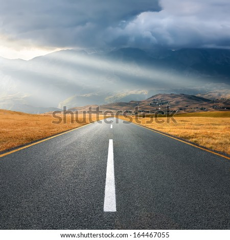 Driving on an empty asphalt road towards the mountain - stock photo