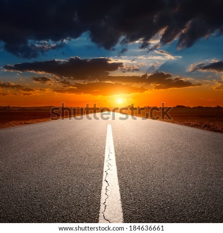 Driving on an empty asphalt road towards the setting sun - stock photo