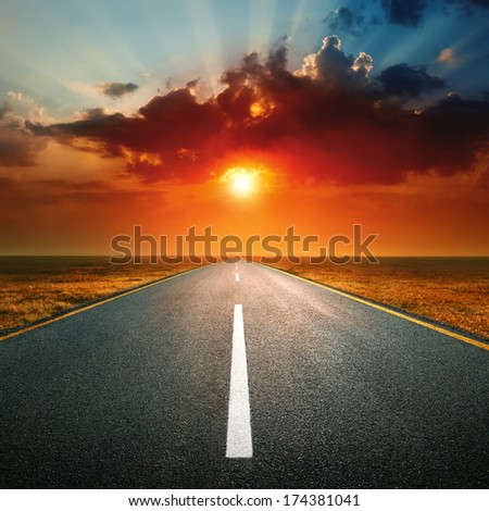 Driving on an empty highway against the setting sun - stock photo