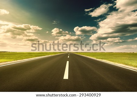 Driving on an empty new asphalt road through the agricultural green fields at sunset. - stock photo