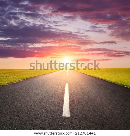 Driving on an empty road against the rising sun - stock photo