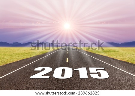 Driving on an empty road at sunset to upcoming 2015 - stock photo