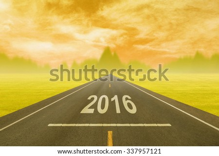 Driving on an empty road at sunset to upcoming 2016 new year - stock photo