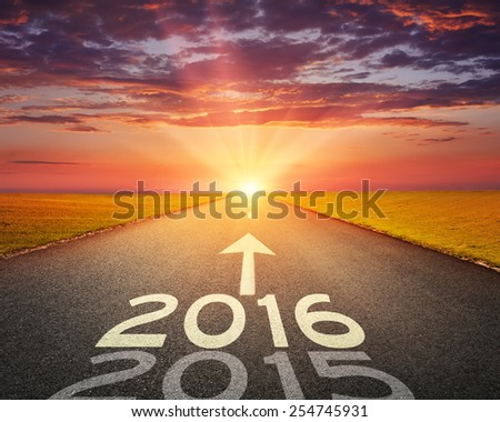 Driving on an empty road towards the setting sun to upcoming 2016 and leaving behind old 2015. - stock photo