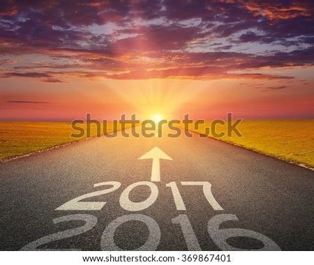Driving on an empty road towards the setting sun to upcoming 2017 and leaving behind old 2016. Concept for success and passing time. - stock photo
