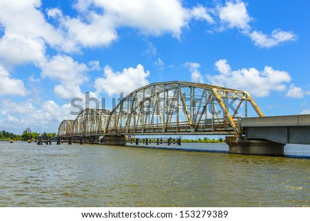 driving on Chef Menteur Highway with old bridge in East area of New Orleans crossing the bay - stock photo