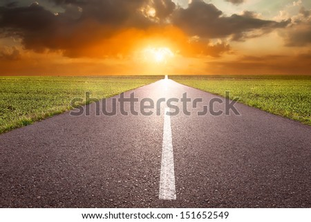 Driving on empty road at red sunset - stock photo