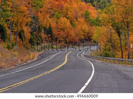 Driving on remote road with Autumn foliage with red, orange and yellow fall colors in a Northeast forest