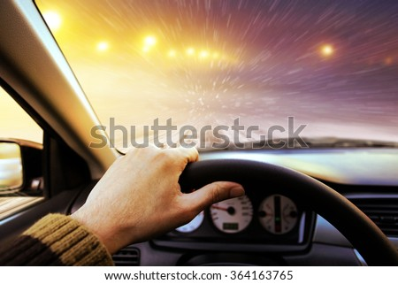 Driving on snow covered winter road with shining streetlights at night - stock photo