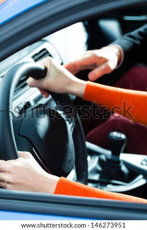 Driving School - Young woman steer a car with the steering wheel, maybe she has a driving test perhaps she exercises the parking - stock photo