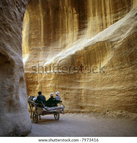 Driving through the Siq in the old city of Petra in Jordan.This city was carved out the rocks. It is now an UNESCO World Heritage site. - stock photo