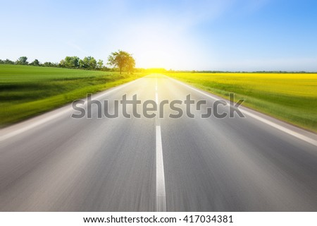 Driving to the sun. Beautiful yellow field countryside landscape