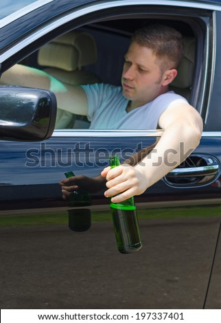 Driving Under the Influence. Male hand with bottle of beer. - stock photo