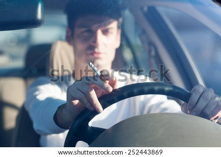 driving while holding a cigarette in hand - stock photo