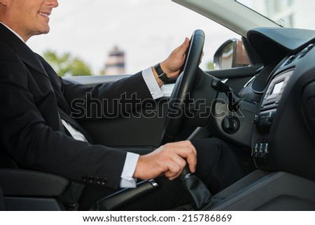 Driving with comfort. Close-up of cheerful mature man in formalwear driving car and smiling - stock photo