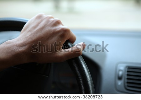 Driving - young man's hand holding the steering wheel - stock photo