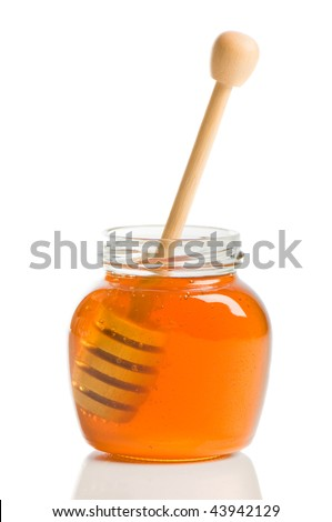 Drizzle stick inside a jar of organic honey on white background - stock photo