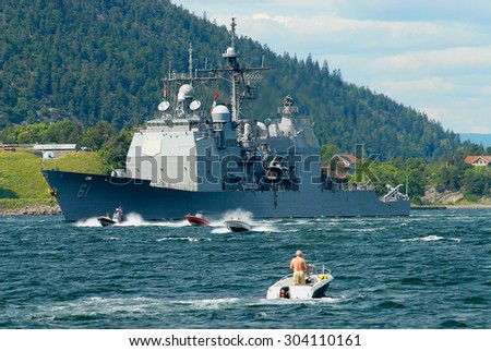 DROBAK, NORWAY - JULY 08, 2006: Unidentified people in motorboats follow norwegian military ship in a fjord in Drobak, Norway. - stock photo